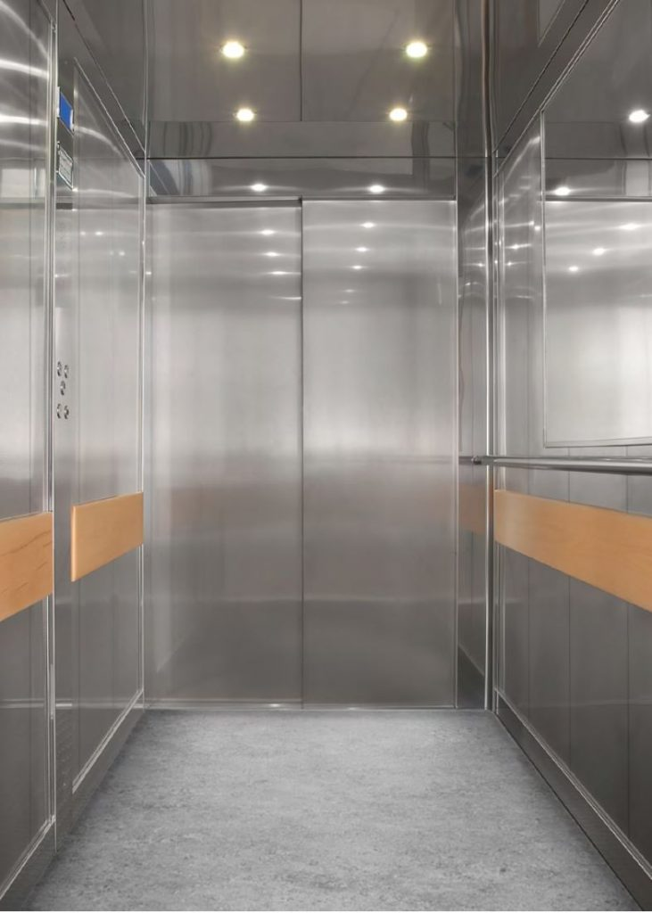 Large stainless steel lift cabin with wood handrails and LED lights on ceiling.