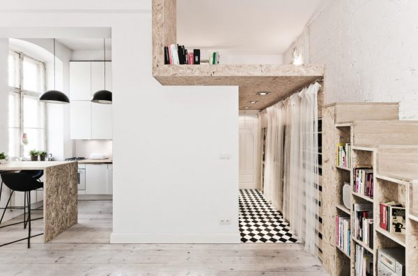 Mezzanine floor in tiny house. Image shows a 29sqm apartment with minimalistic styling. The mezzanine floor is built above the entry way and accessed via steps that double as storage space. Mezzanine creates private bedroom away from the living areas of the apartment.