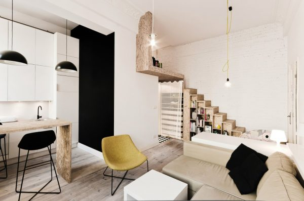 Mezzanine level for small apartment. Mezzanine Inspiration for tiny homes. Shows how mezzanine level does not take away from the design or space of the ground level while maximising space in small home. Bookcase doubles as stairs to access mezzanine.