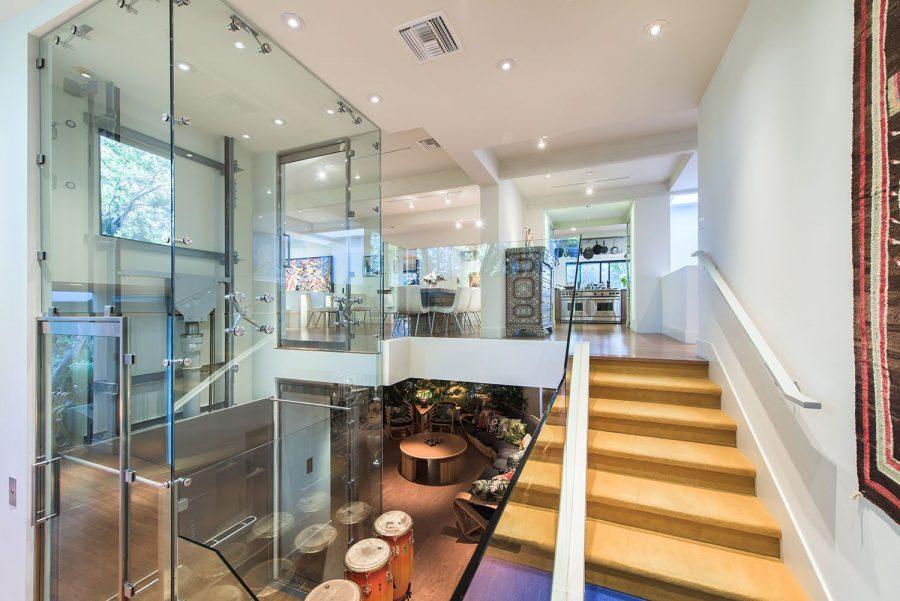 Image shows mezzanine accessible via lift. Stylish glass elevator and staircase providing access to mezzanine floor in celebrity home. Mezzanine Elevator Inspiration.