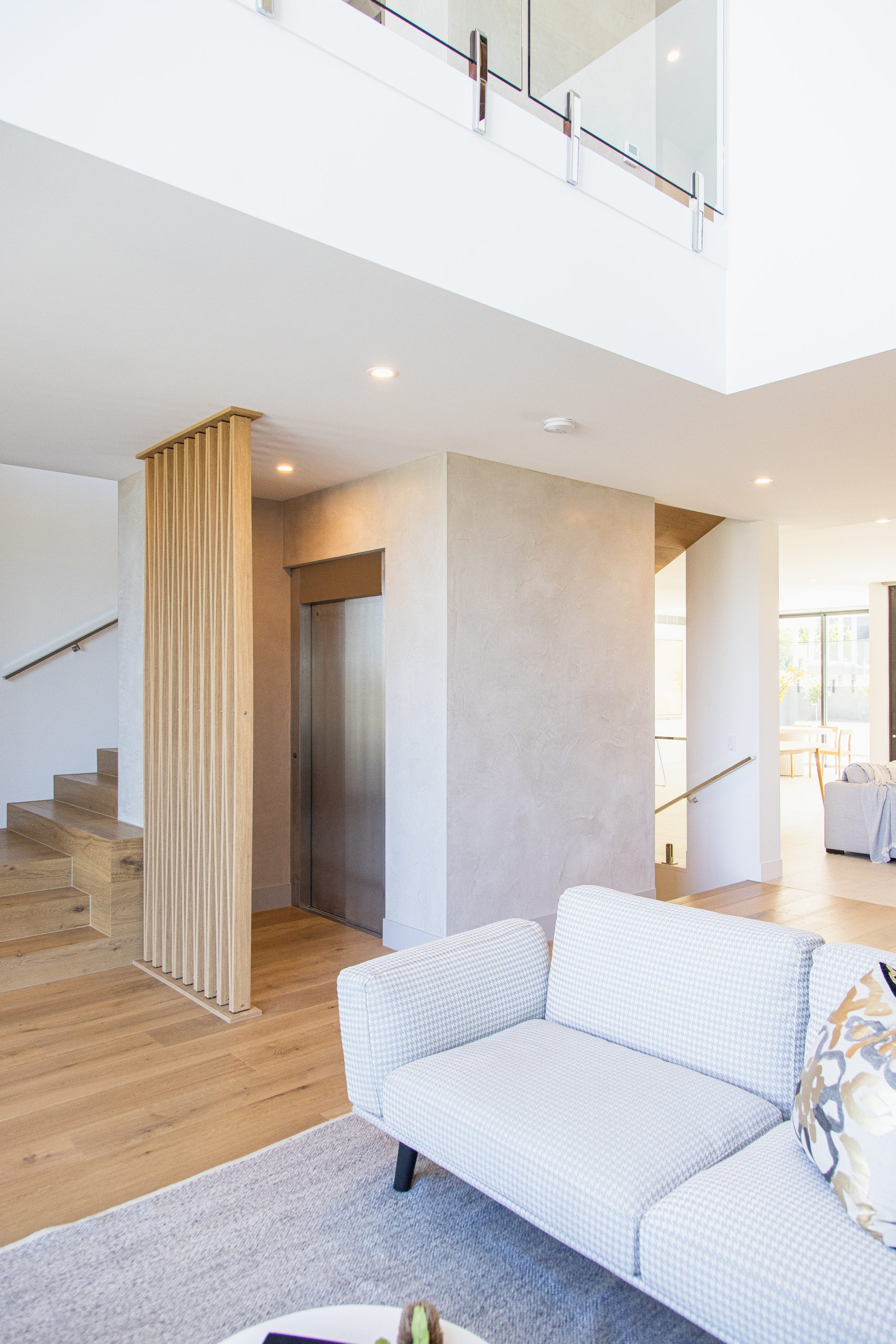 a modern living area with stylish elevator shaft next to the staircase. The elevator door is silver metal and the shaft is white. there is a wood structure in front of the elevator.