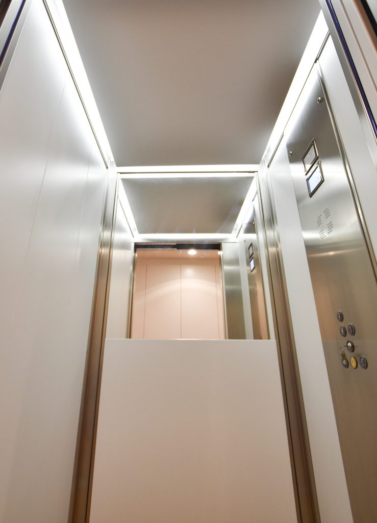 Interior shot of a residential jewel home lift with half height mirrors.