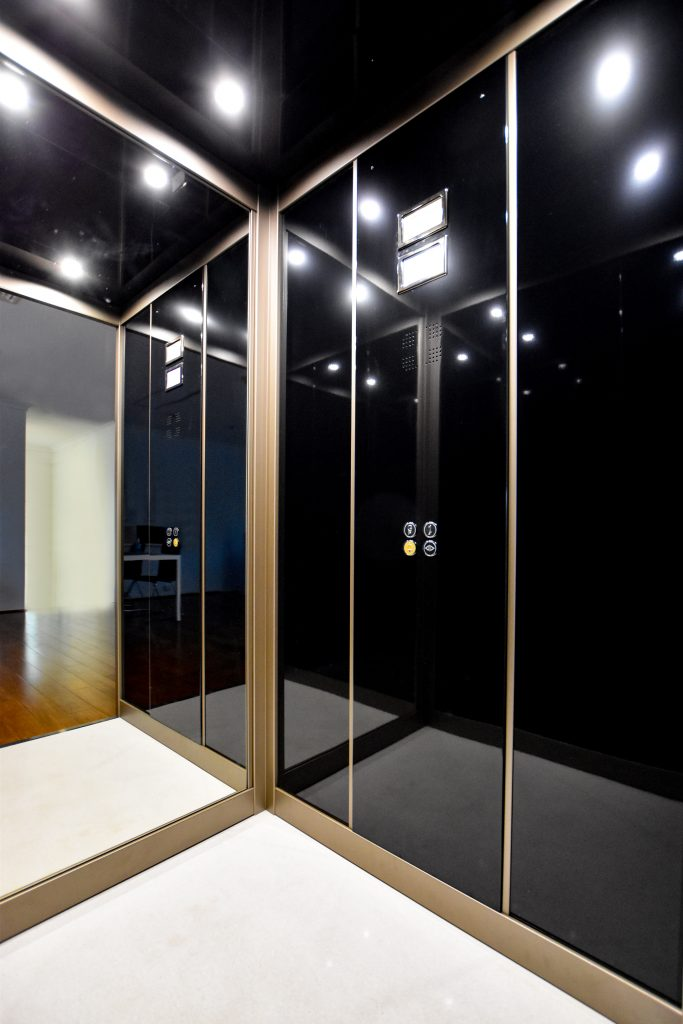 A stylish home lift with a black reflective skin plate and gold detailing