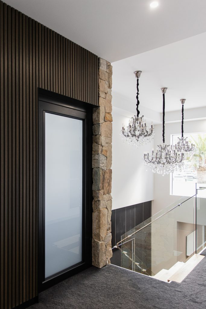 Residential sovereign home lift with a custom stone feature wall