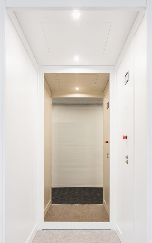 sleek minimalist classic home lift with all white walls and custom flooring