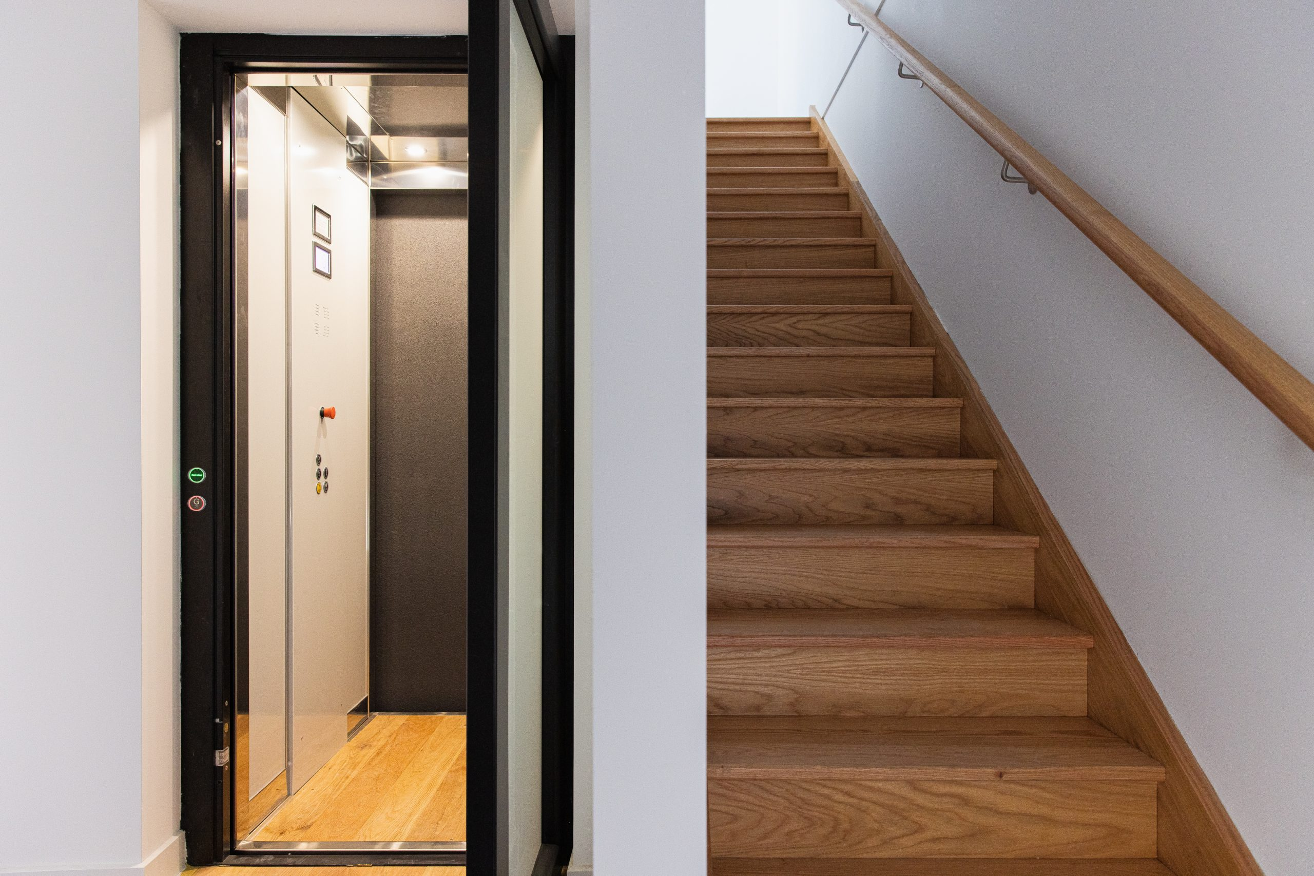 black rimmed lift with white walls and wooden flooring, next to a staircase.