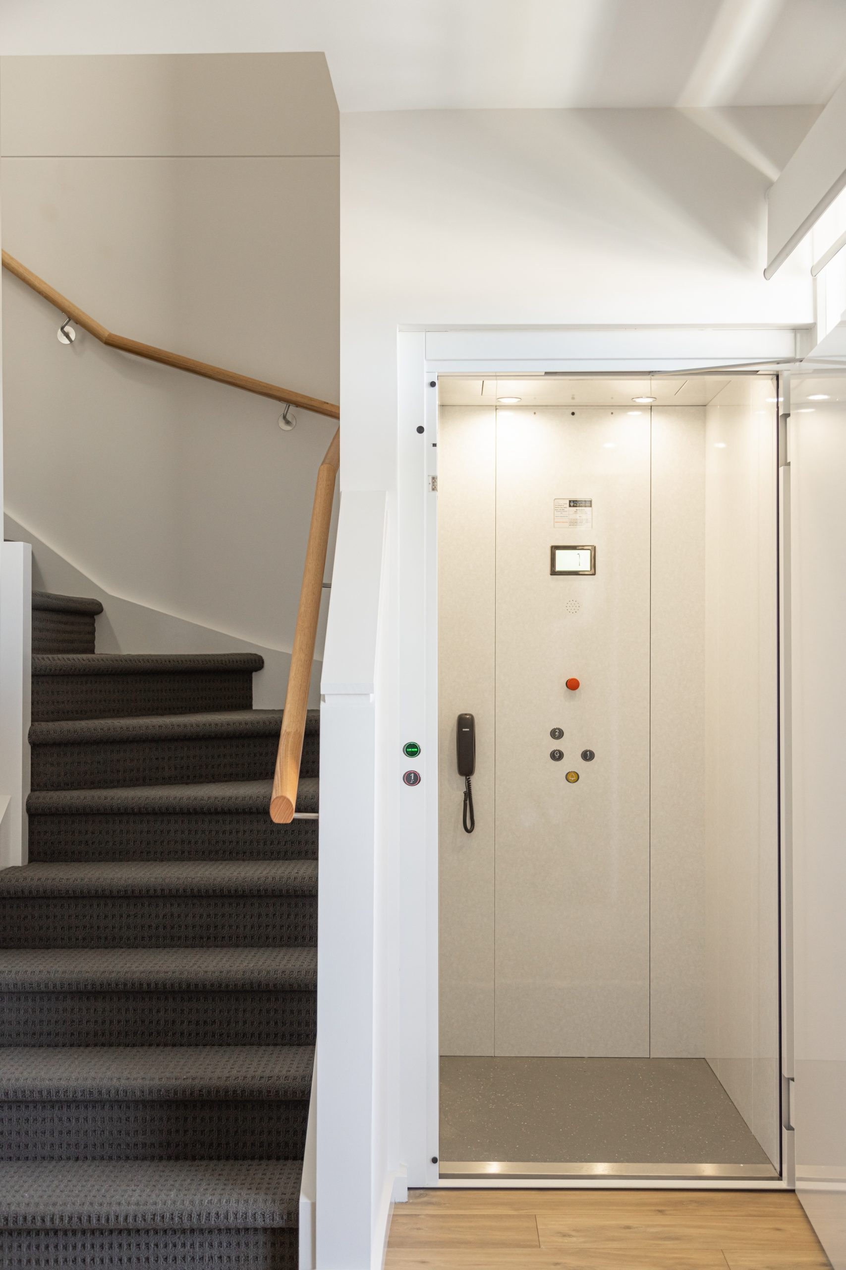 white cabin residential elevator with wooden floors next to a staircase.