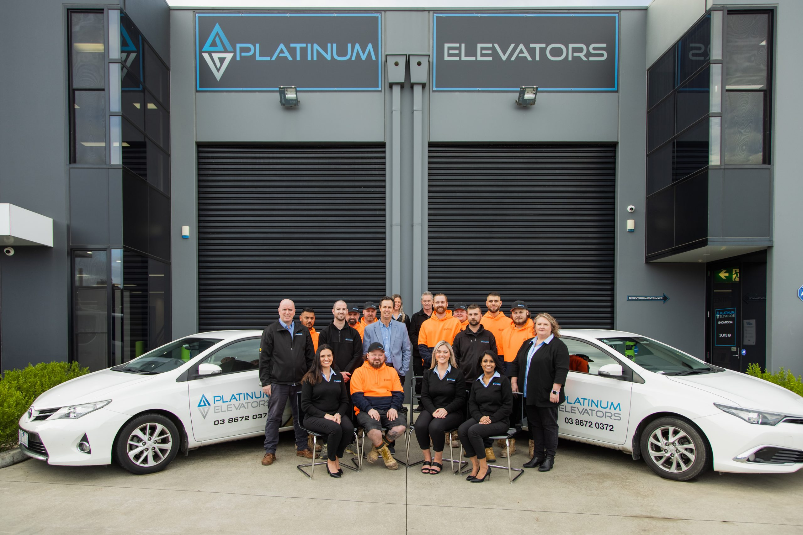 Platinum Elevators Sales and Installation team in front of the company cars and showroom.