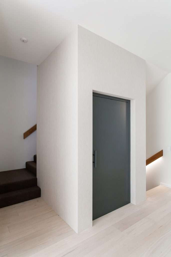 A white lift shaft with a blue door sits in between two staircases in a home.