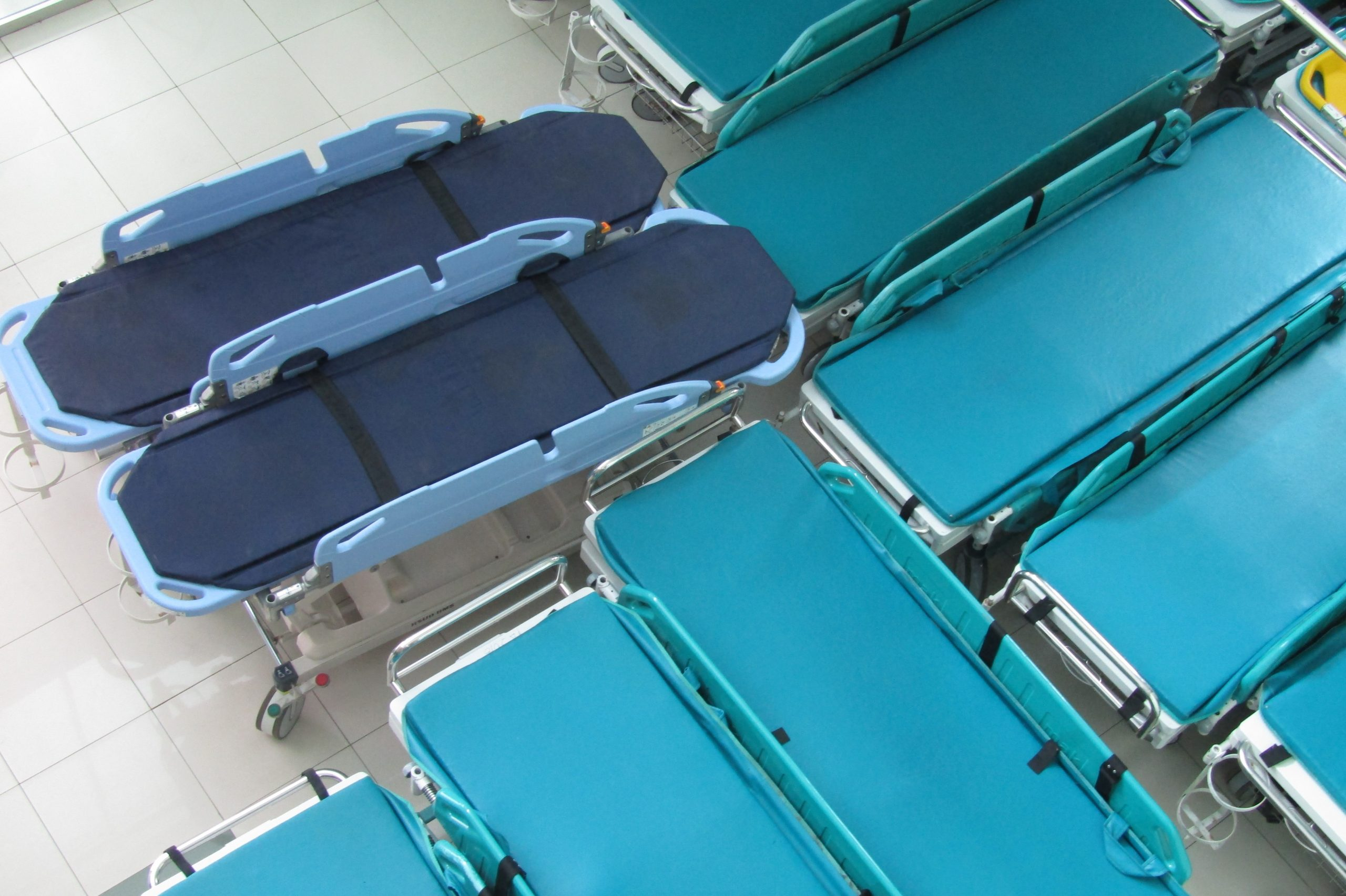 blue ambulance stretcher beds are grouped together in a hospital room.