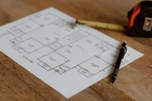 house floor plan lays on wooden bench with a pen and measuring tape