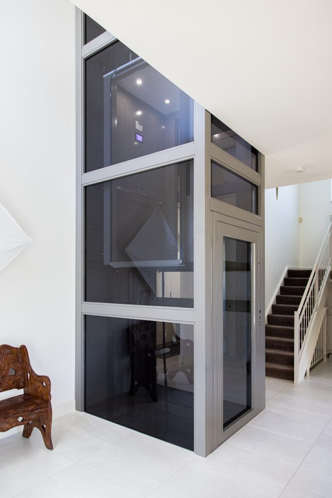 a metal glazed lift shaft protrudes from the white melbourne living room.