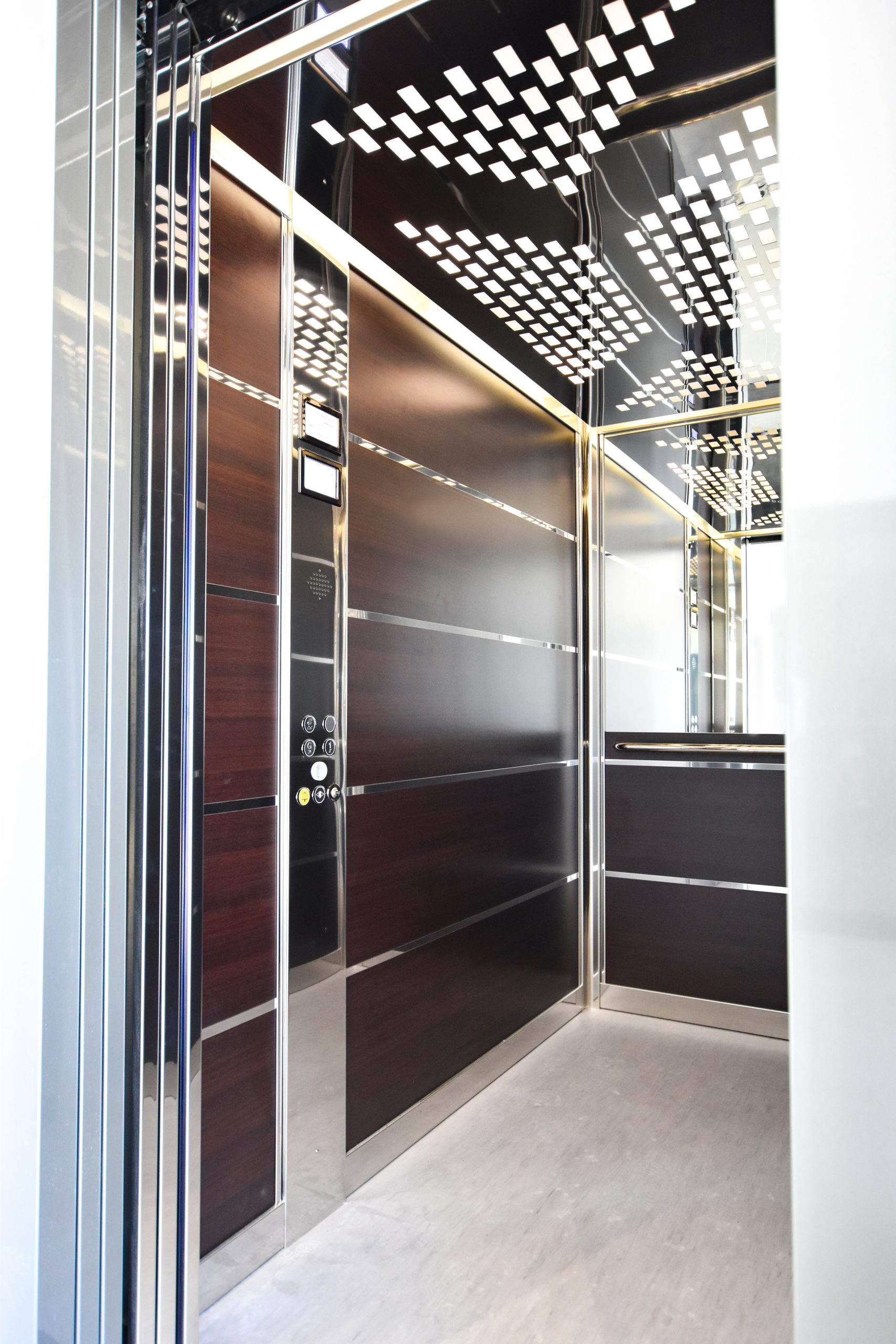 a brown stretcher lift cabin with silver details, a half length mirror on the far wall, lights on the ceiling and a light floor.