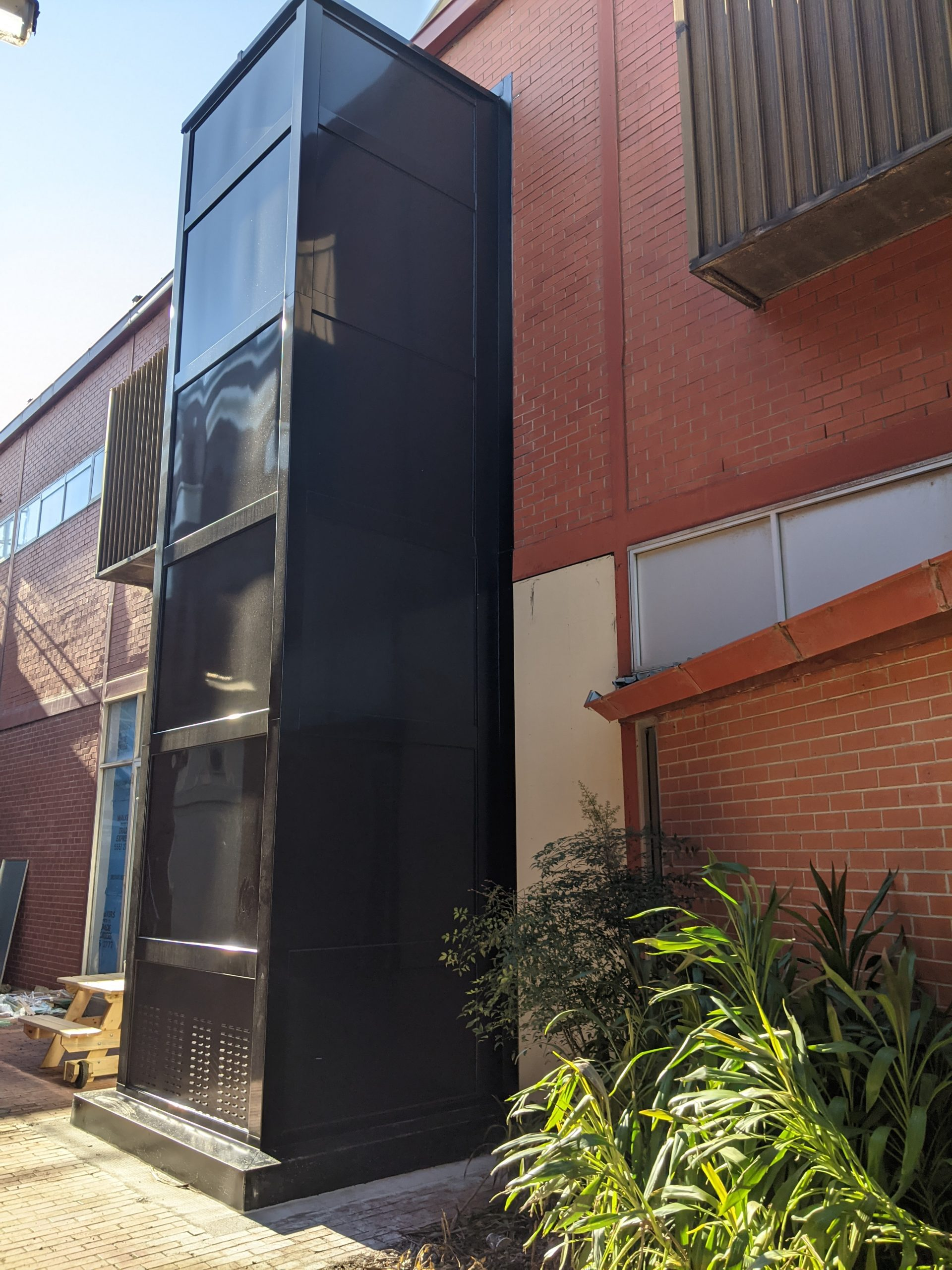 an black metal structure elevator attached to the exterior wall of a building