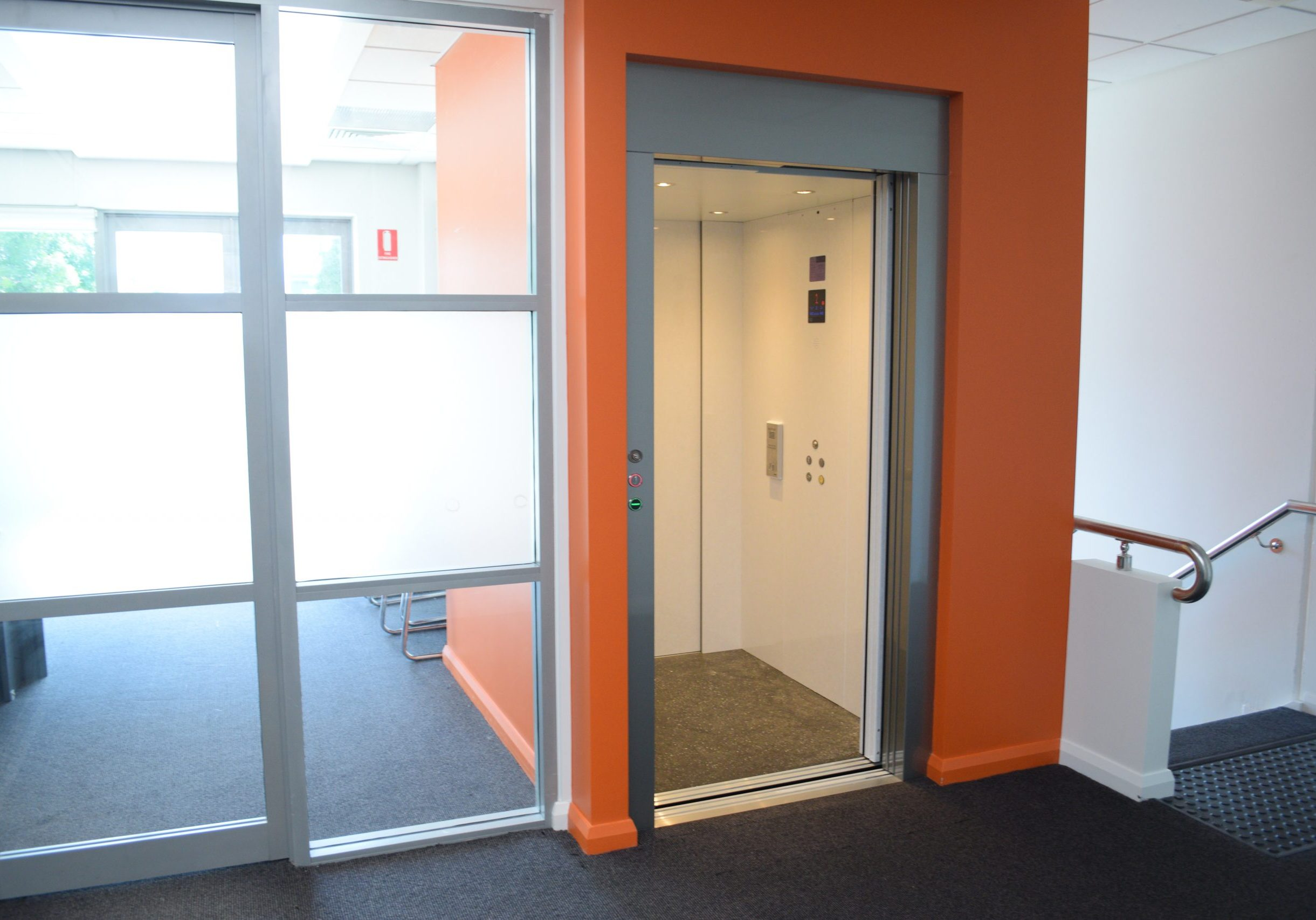 an open door elevator with an orange shaft, silver metal frame and white cabin walls.