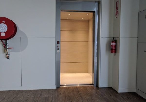Commercial elevator in Cowes with an open door. The cabin is cream coloured with light oak wood on the back wall. The frame is a silver metal. there is a fire hose to the left of the lift.