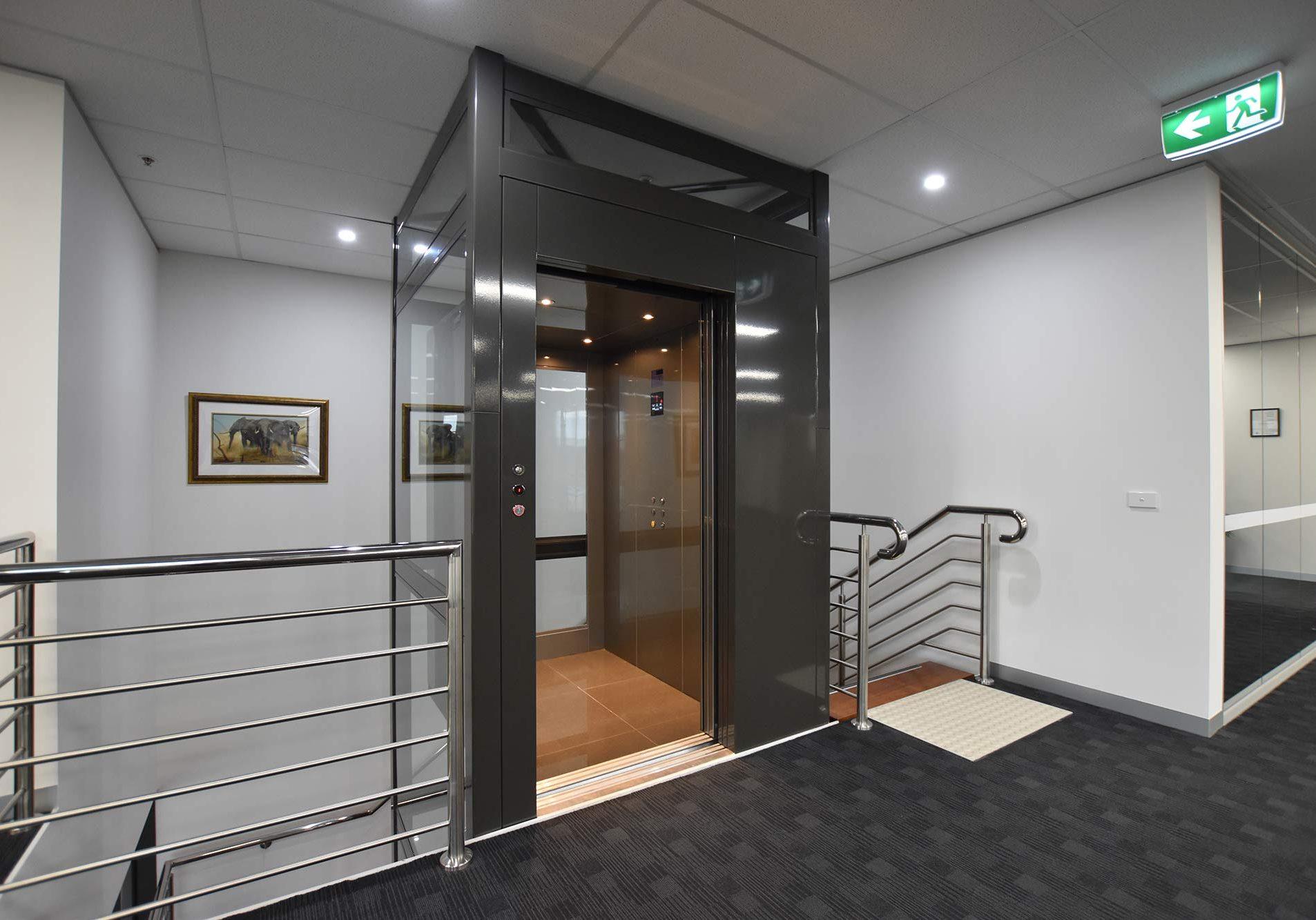 a commercial elevator in a glazed metal structure with clear glass doors and walls. the floor of the elevator is wood. there are metal handrails and stairs which wrap around the lift shaft.