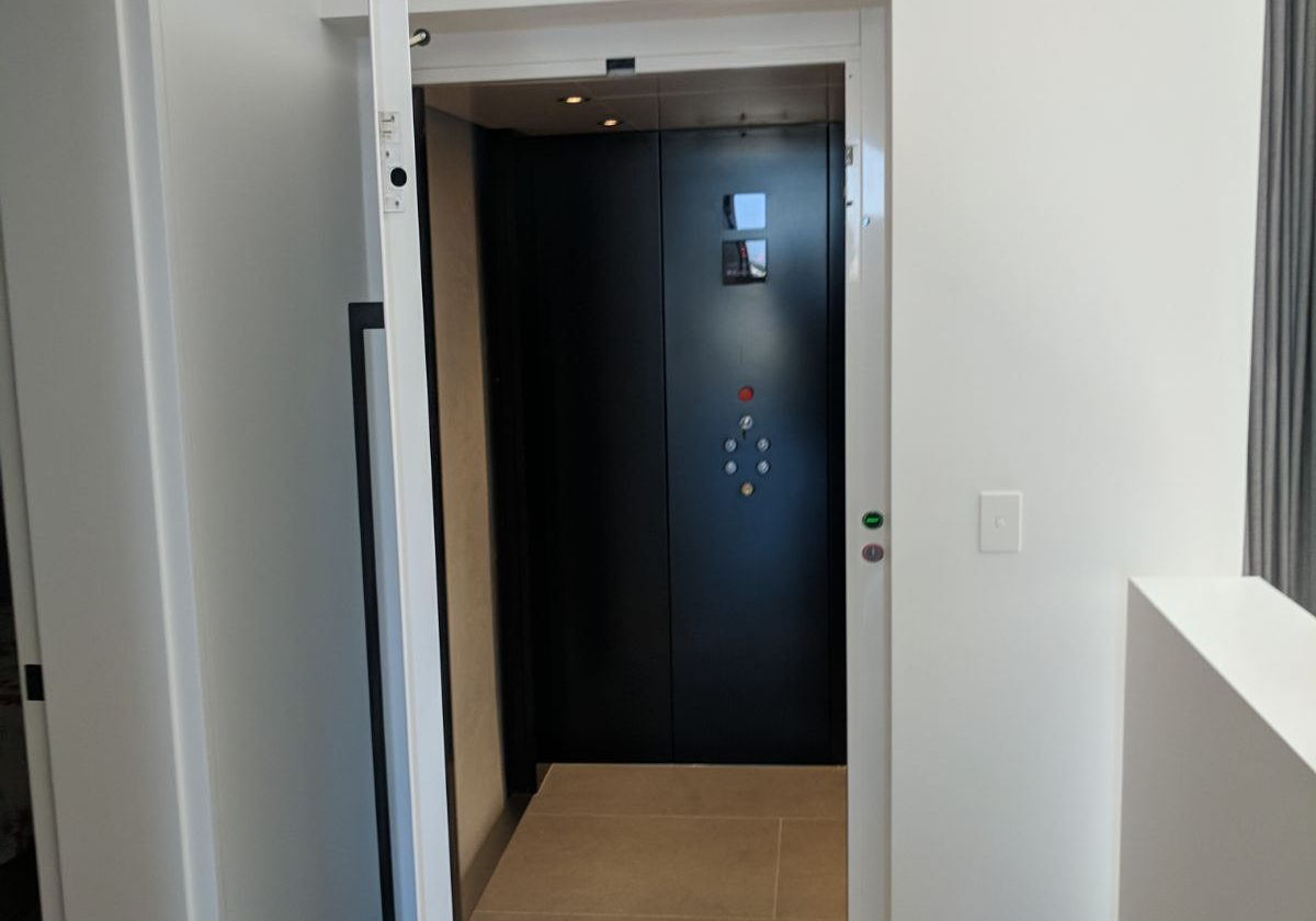 An elevator in Northcote with light wooden floors and neutral tones for it's lift shaft's exterior walls.