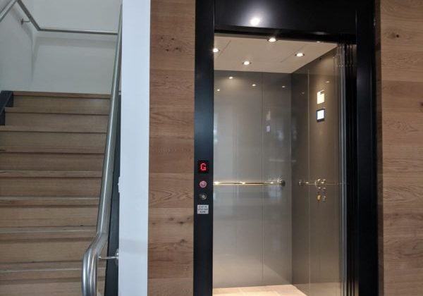 an open door elevator with a black metal frame in a commercial building. The walls of the building are light oak and the floors are polished grey concrete. there is a staircase to the left of the elevator. the lift cabin has grey walls and light oak floors.