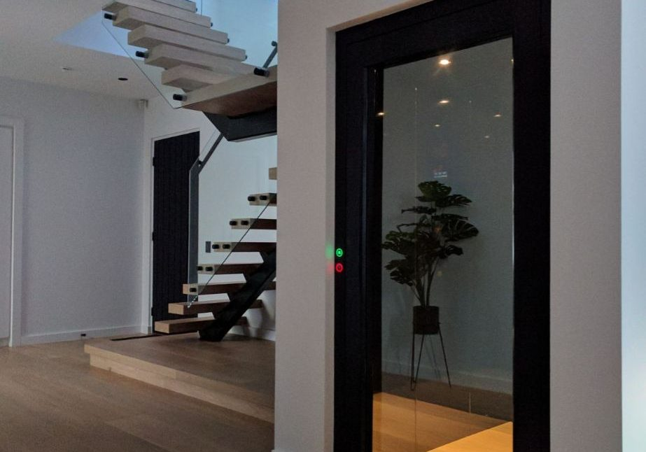 A beautoful modern home featuring wooden floors, a floating staircase and feature elevator with a reflective door