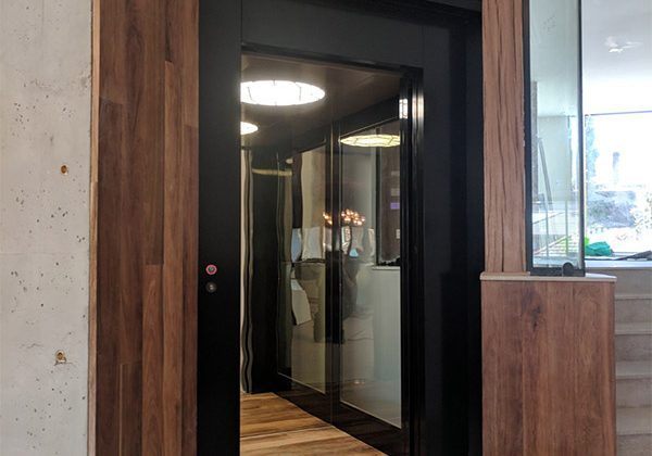 A striking elevator design inspired by dark wood, black and reflective surfaces.