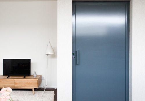 A dark blue elevator door nestled in a Brighton home featuring modern white walls