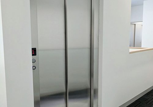 A closed door commercial lift with a metal frame and doors.