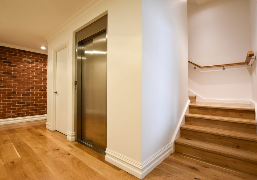 Home lift installed adjacent to stairs in the stairwell void