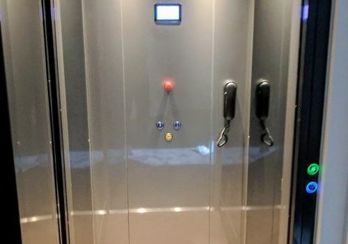 a lift with a black frame, clear glazed class door, grey walls and wooden floors. the back wall has a control panel and phone.