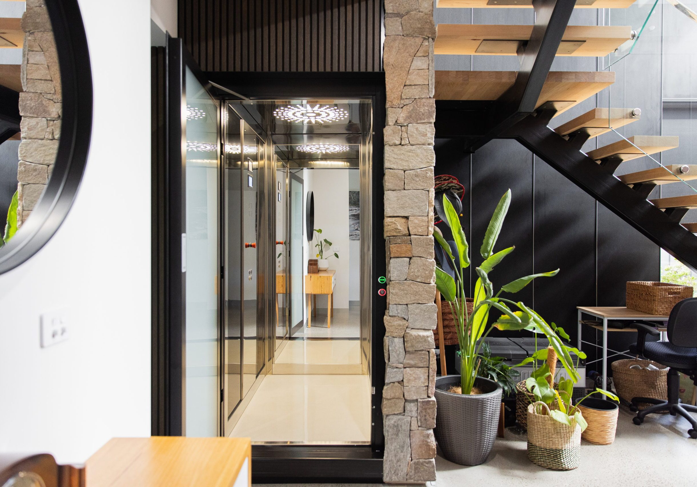 home elevator with open door, full length mirror on back wall and digital display. shaft is timber and render with stone tiles.