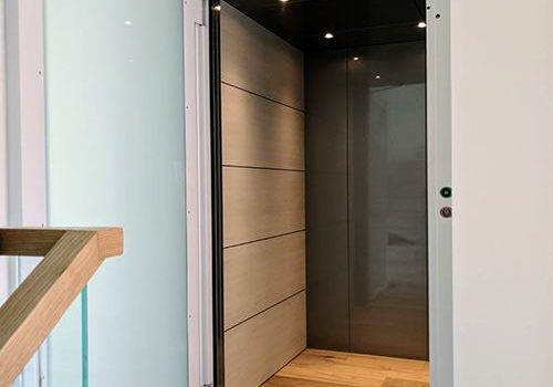 an open door lift with a white frame. The door is opaque glass with a light blue tint. the floor and side walls of the lift are light wood and back wall and roof are black.