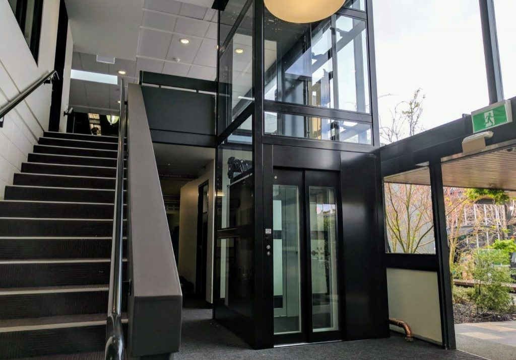 crown commercial lift in a dark colour and with glass doors