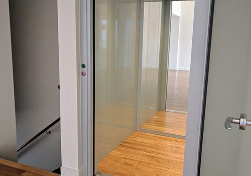 Open door of a new residential lift installed in Dromana. the lift frame is grey and the doors are clear glass. the floor is wood and the walls are a grey/green colour.