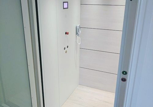 a white elevator cabin with a grey frame and opaque glass door.
