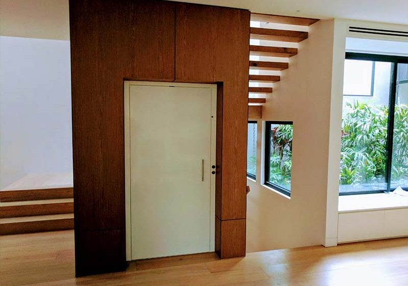a brown elevator shaft with a closed white elevator door. it is located inside a house next to the wrap-around stair case. there are large windows to the right of the staircase and elevator. the floors of the room are light oak wood.