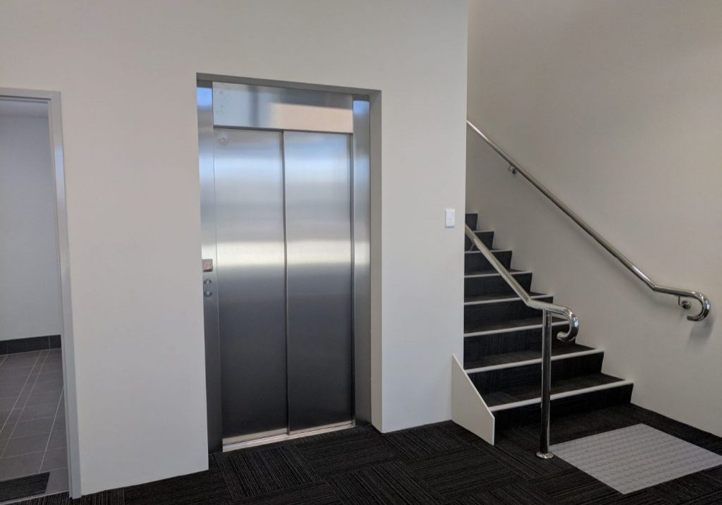 Maxi lift pictured on the ground floor of a Melbourne business to the left of a staircase