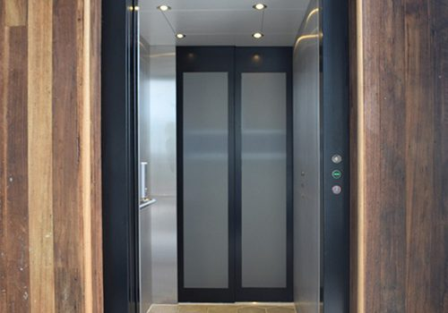 a long elevator with through passage, a clear glass door closest and grey slider doors at the end. the lift is in a dark wood shaft and has a black frame. the walls are grey and the floor is light wood.