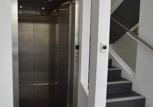 a metal elevator with open doors in a white shaft with office stairs to the right of it.