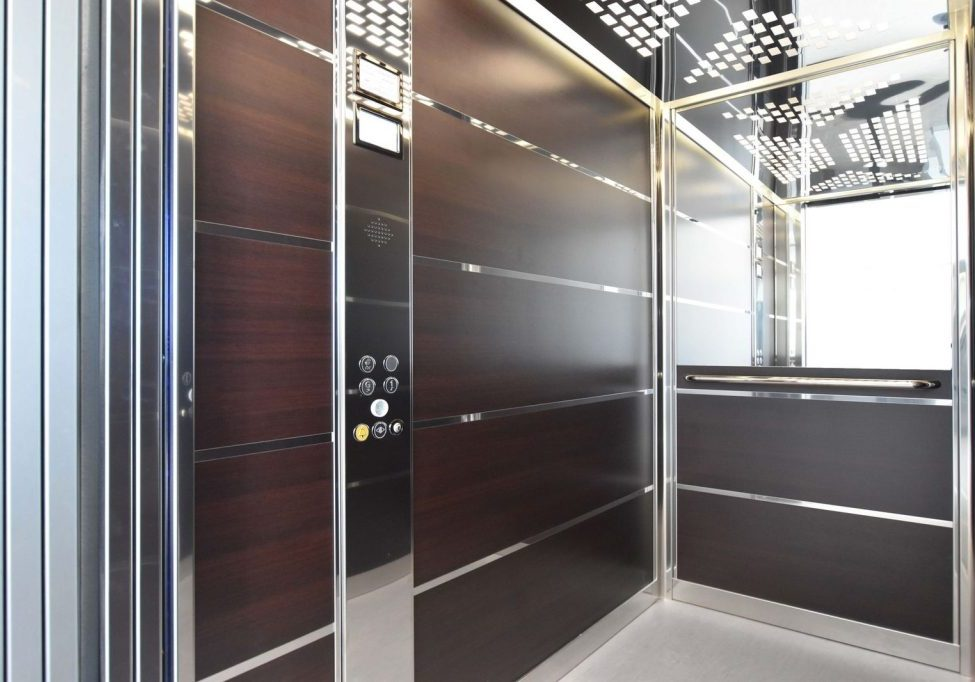 Large lift cabin with wood panelling and designer lights