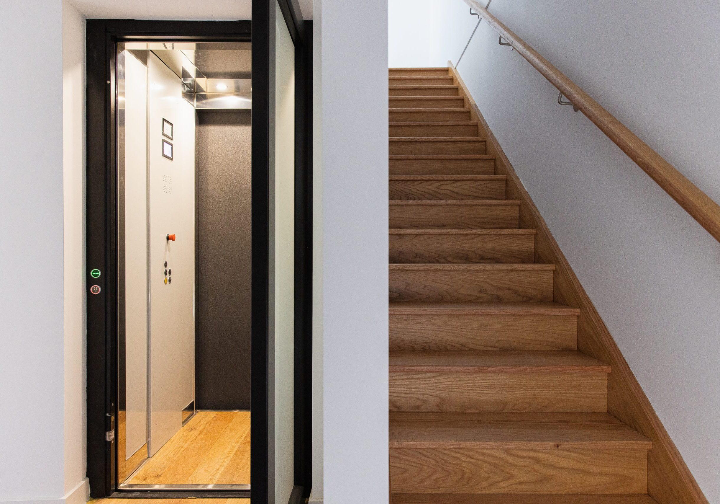 open door elevator with a dark frame and wooden floors next to a wooden staircase.