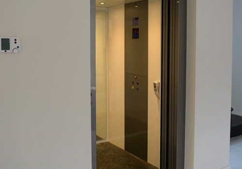 an elevator with a closed glass door with a grey metal frame. the cabin interiors have white walls, with grey accents, a control panel and led lights.