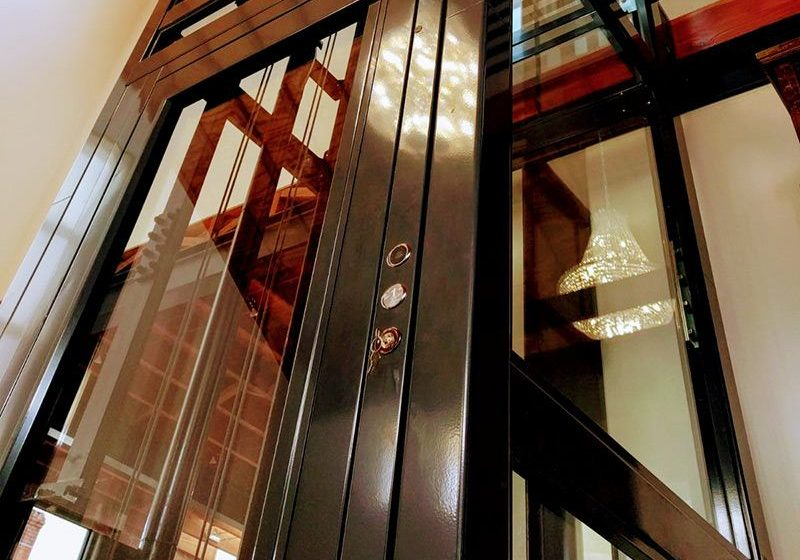 angled image of a lift's glazed brown metal structure, door and ropes. The walls of the structure are transparent glass.