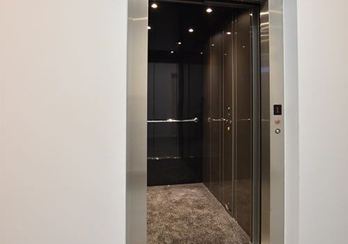an elevator has open doors and a silver metal frame. inside the cabin are dark polished walls, brown flooring and a handrail.